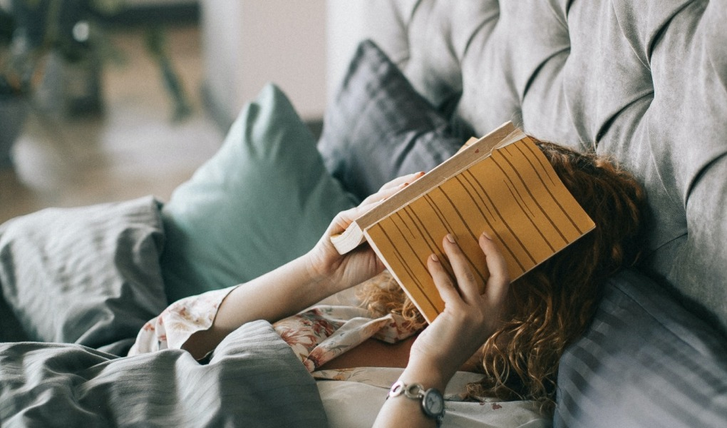 woman covering face with book on bed 1524232 1020x600 - Is Your Bedroom Set Up For Sleeping?