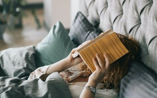 woman covering face with book on bed 1524232 320x200 - Is Your Bedroom Set Up For Sleeping?